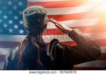 Veterans Day, Memorial Day, Independence Day. A Female Soldier Salutes Against The Background Of The