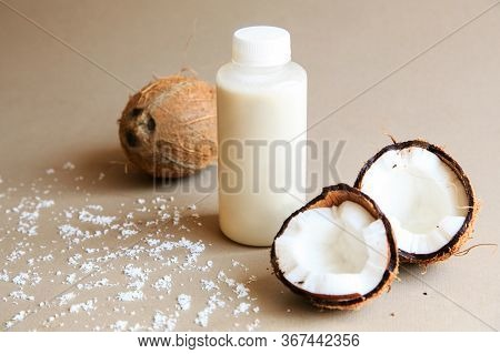 Coconuts And A Jar Of Coconut Milk On Background. Cut Tasty Coconuts And A Bottle Full Of Delicious