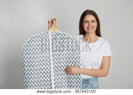 Young Woman Holding Hanger With Clothes In Garment Cover On Light Grey Background. Dry-cleaning Serv