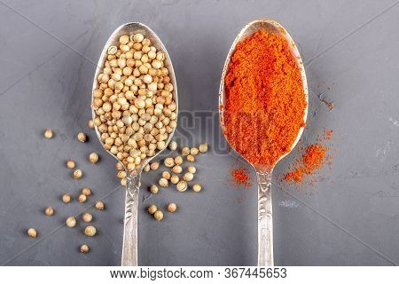 Closeup Coriander Seeds And Ground Paprika In Teaspoons