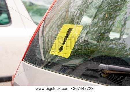 A Yellow Exclamation Mark On The Rear Window Of A Car. Inexperienced Driver Concept. Sign Of An Inex