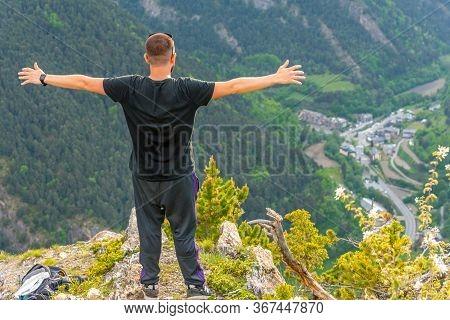 La Massana, Andorra: May 20, 2020: Man On A Stone Above The City Of La Massana In The Principality O