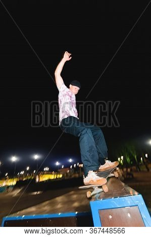 A Young Skater Does The Trick Of Sliding At Night In A Skatepark Amid The Burning Lights Of Lighting