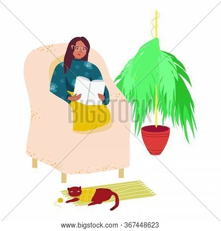 A Woman Is Sitting In A Chair And Reading A Book. A Young Woman Or Teenager Is Relaxing In A Chair A