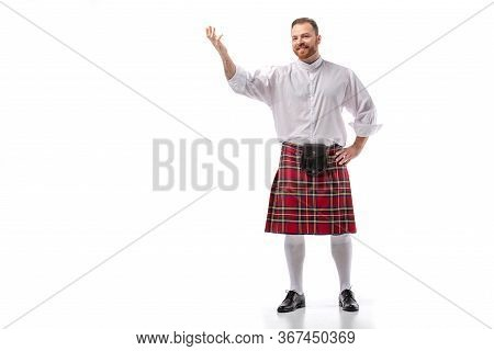 Smiling Scottish Redhead Man In Red Kilt Pointing With Hand On White Background