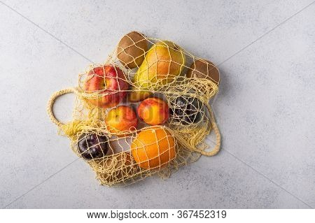 Fruits In The Range In Yellow Eco String Bag On A Light Wooden Surface. Environmental Protection Con