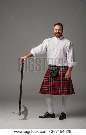 Smiling Scottish Redhead Man In Red Kilt With Battle Axe On Grey Background