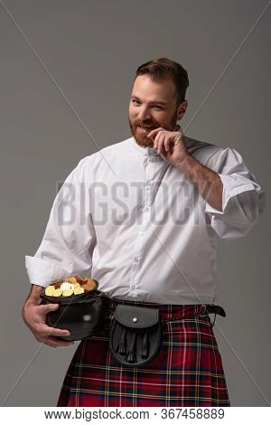 Scottish Redhead Man In Red Kilt Holding Potty With Gold Coins Isolated On Grey