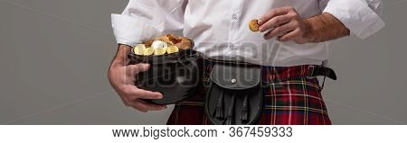 Cropped View Of Scottish Man In Red Kilt Holding Potty With Gold Coins On Grey Background, Panoramic