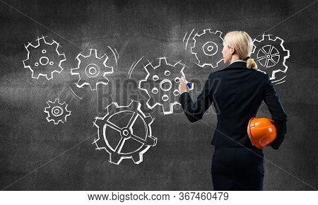 Businesswoman Draws Gears Mechanism On Blackboard. Back View Woman In Business Suit With Safety Helm