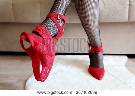 Female Legs With Removed Red Panties. Woman In Black Fishnet Stockings And Shoes Sitting On A Sofa,