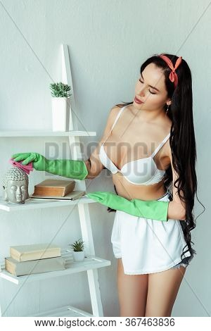 Seductive Woman In Rubber Gloves Cleaning Decorative Statuette On Rack At Home