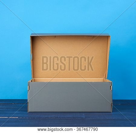 Empty Open Cardboard Box For Shoes On A Blue Background, Close Up