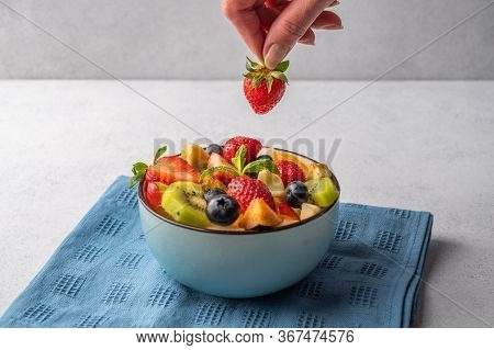 Salad From A Mixture Of Different Fruits. Womans Hand Holds Strawberries. Copy Space For Text