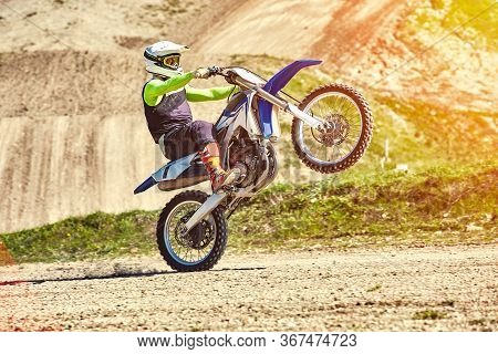 Motocross, A Rider Stands On The Rear Wheel Of A Bike, Riding On The Rear Wheel. Extreme, Industrial