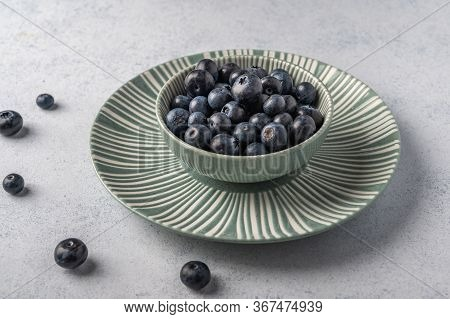 Blueberries Into Bowl On A Plate On A Light Wooden Background. Top View. Copy Space For Text
