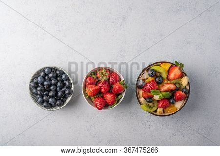 Fresh Fruit Salad With Different Ingredients On Light Wooden Background. Healthy Diet. Copy Space Fo