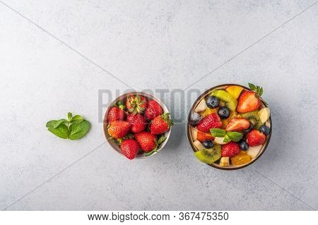 Fresh Fruit Salad With Different Ingredients And Mint On Light Background. Healthy Diet. Copy Space