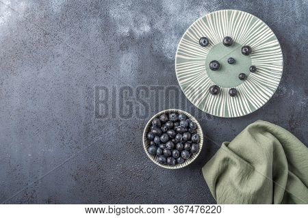 Blueberries Into Bowl On A Plate With Napkin On A Dark Wooden Background. Top View. Copy Space For T