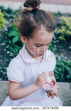 Cute Toddler Girl Eating Ice Cream With Spoon Sitting Outdoor. Real Life Moments.