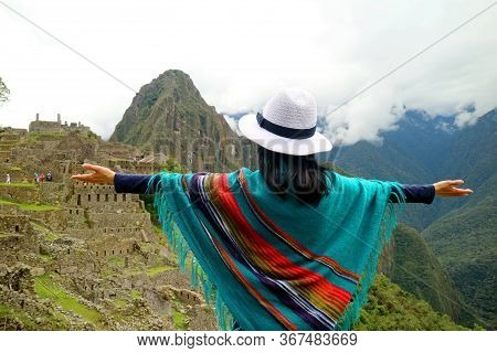 Female Traveler In Poncho Opening Arms To The Incredible Ancient Inca Citadel Of Machu Picchu, Unesc