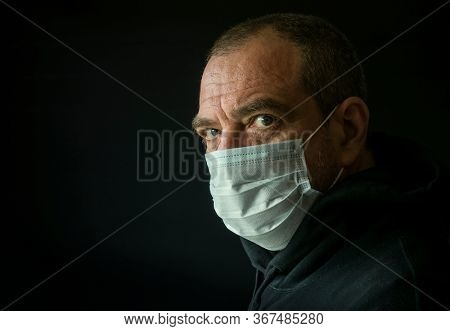 Adult man in facial medical mask on a black background, close-up face