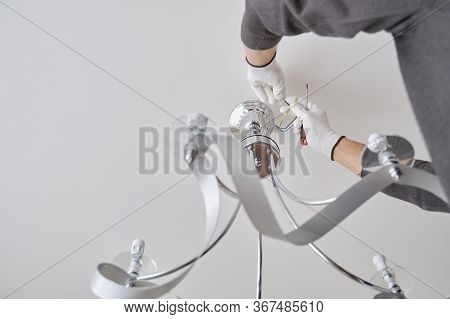 Installation Ceiling Lamp, Hands Of Male Electrician Fixing Chandelier With Use Of Professional Tool