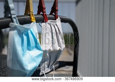 Surgical Face Mask For Coronavirus Hanging On Clothesline String With Clothespin
