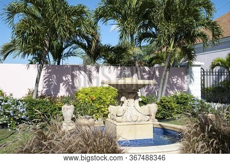 The Little Fountain Surrounded By Tropical Greenery In Nassau Downtown Square (bahamas).