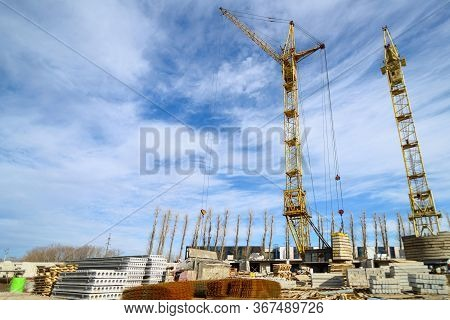 Photos Of High-rise Construction Cranes And An Unfinished House Against A Blue Sky. Photographed On