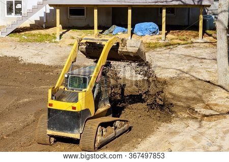 Mini Bulldozer Landscaping Works On Construction Working With Earth While Doing Scoop Excavator