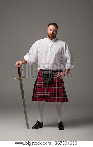 Scottish Redhead Man In Red Kilt With Sword On Grey Background