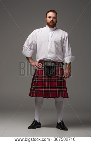 Scottish Redhead Man In Red Kilt With Hand On Hip On Grey Background