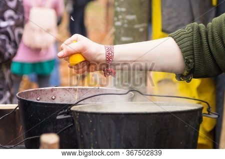 Cooking Mulled Wine Outdoor: A Female Hand Squeezes An Orange Into A Vat Of Mulled Wine