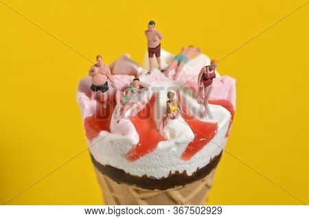 Ice Cream In Waffle Cone And Miniature People On Beach