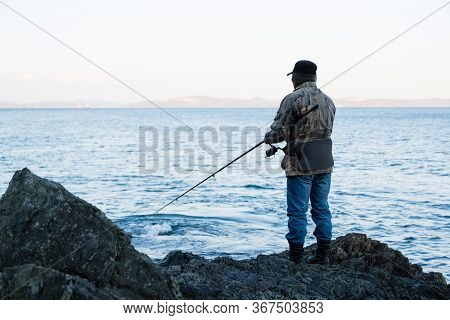 Fisherman on evening fishing on the rocks by the sea