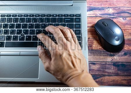 Laptop With A Hand While Typing Or Encoding And Moving Mouse. Business Concept, Office Concept, Work