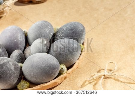 Black Glistening Eggs (colored By Red Wine) On A Clay Plate Beside Jute Rope Bow On A Brown Table. E