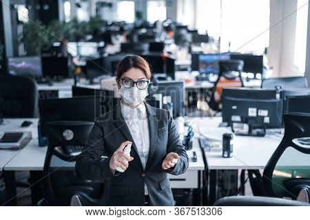 Female Manager In A Medical Mask Sprays On Hand Antiseptic. A Woman In A Suit Uses A Sanitizer To Di