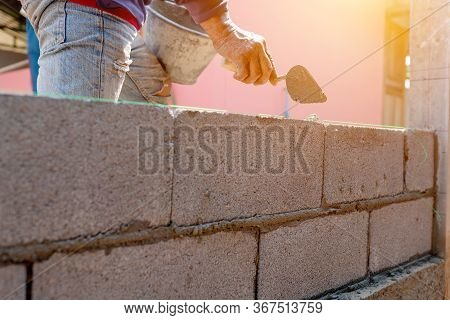 Bricklayer Working On The Construction Of The Wall Or Walls Of The Building.
