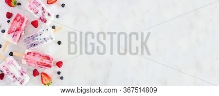 Assorted Berry Fruit Yogurt Popsicles. Above View Side Border On A White Marble Banner Background Wi