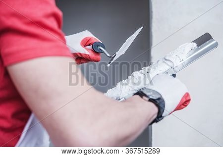 Close Up Of Construction Male Worker Applying Thin Coat Of Drywall Compound Using Professional Tapin