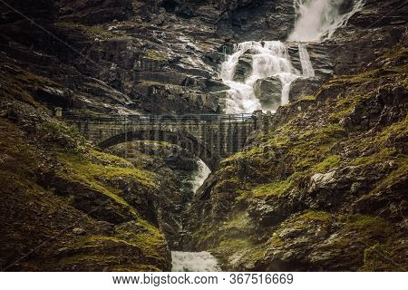 Majestic View Of Trollstigen Road In Norway With Stone Bridge Waterfall And Rough Bouldered Mountain