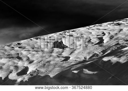 Off-piste Snowy Slope At Windy Winter Night After Snowfall. Black And White Toned Landscape. High Co