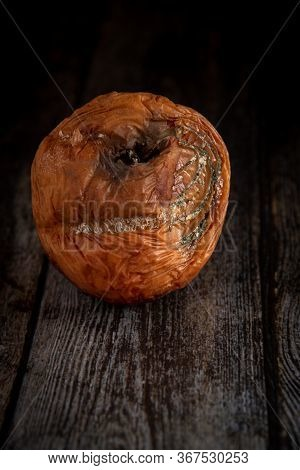Wilted Rotten Apple With Fungus On A Wooden Brown Surface