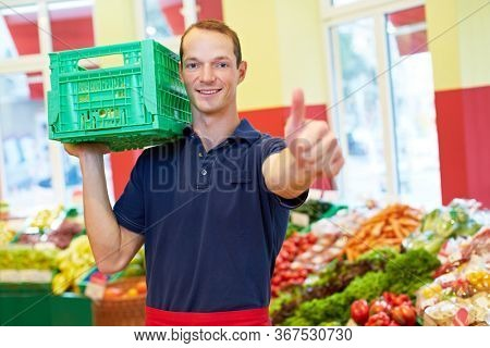 Smiling employee with vegetable crate in the supermarket holds his thumb up
