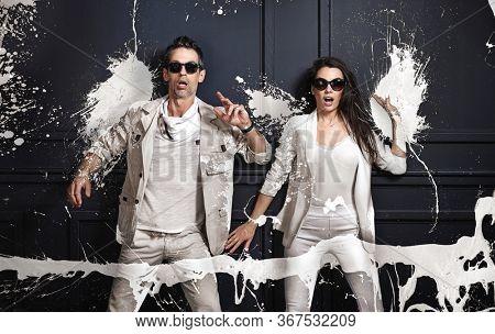 Surprised couple with white paint splash