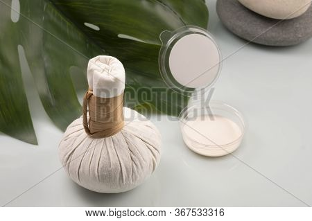 Massage Set Bag With Herbs And Cream Jars In The Background With Leaf Of Monstera