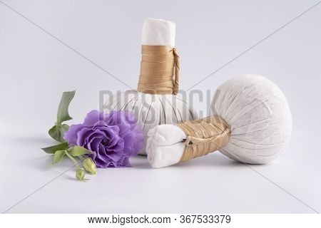 Cosmetic Set For Massage With Bags Of Herbs And Purple Flower On White Background