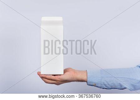 Pak Of Milk On Male Palm On White Background. Copy Space, Mock Up.